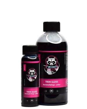 dvě průhledné láhve různé velikosti obsahující černou tekutinu, přípravek určený k ochraně plastů automobilů bez obsahu silikonu Trim Gloss, s etiketou a logem autokosmetiky Racoon Cleaning Products