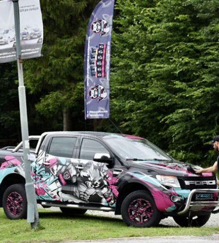 automobil ford Ranger v reklamním polepu Racoon Cleaning Products při čištění jeho majitelem