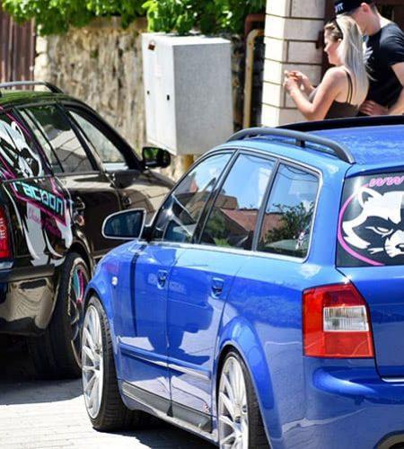tlachající se chlap s blondýnkou při zaparkovaných autech modré audi s4 a škodě octavii černé barvy s reklamním polepem Racoon